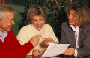 Old Couple Signing Papers With Young Executor